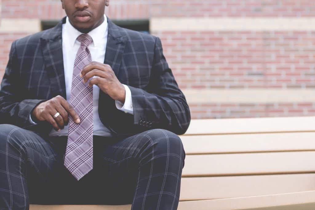 Homem de terno e gravata, sentado no banco, com aliança de prata larga no dedo anelar direito.