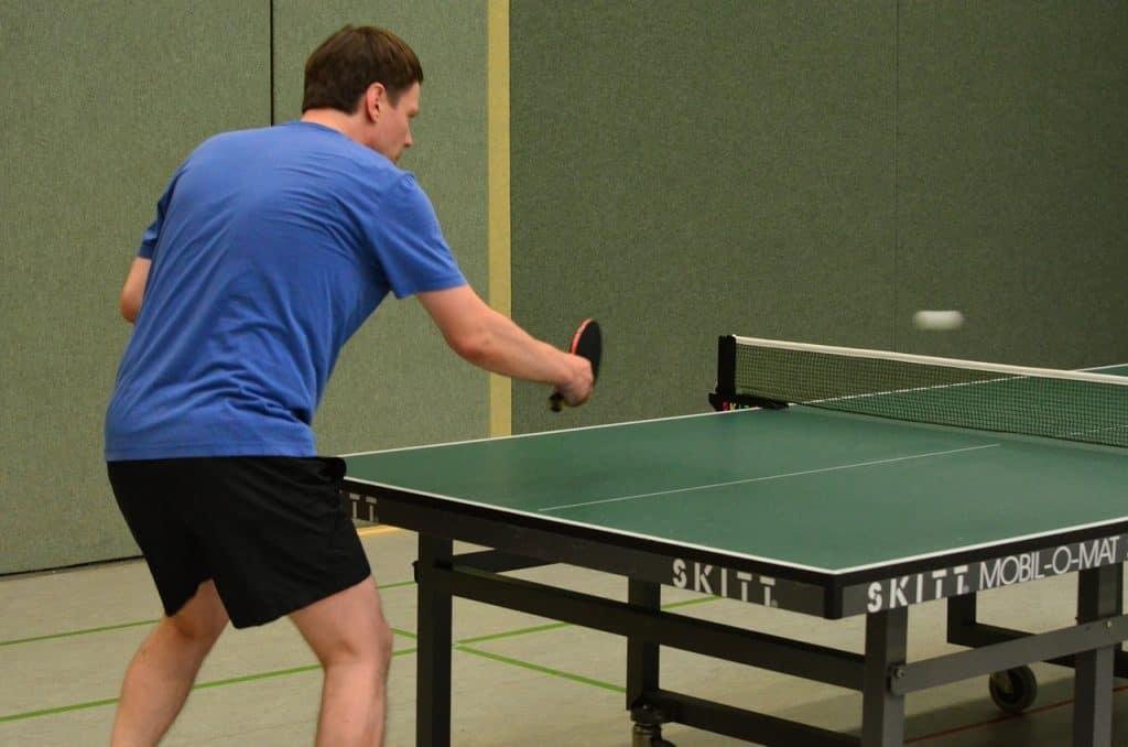 Na foto um homem jogando tênis de mesa.
