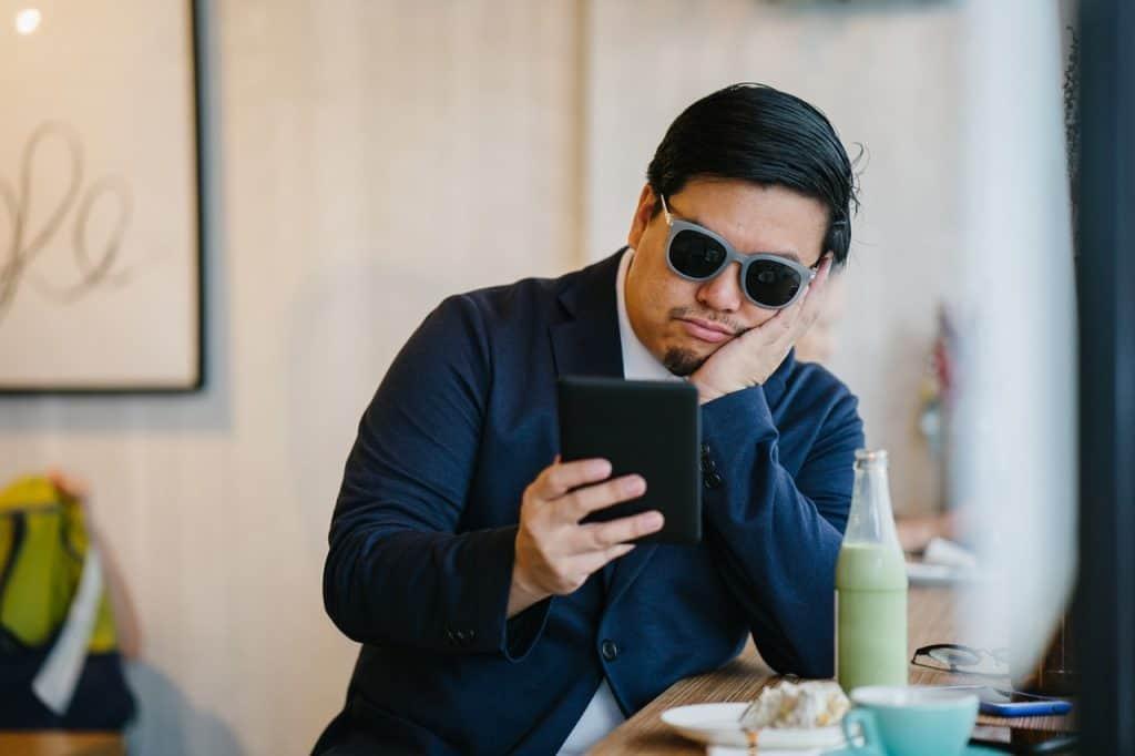 Foto de um homem sentado em uma bancada, com suco e comida à sua frente, lendo ao em um Kindle. Ele veste trajes sociais e óculos escuros.