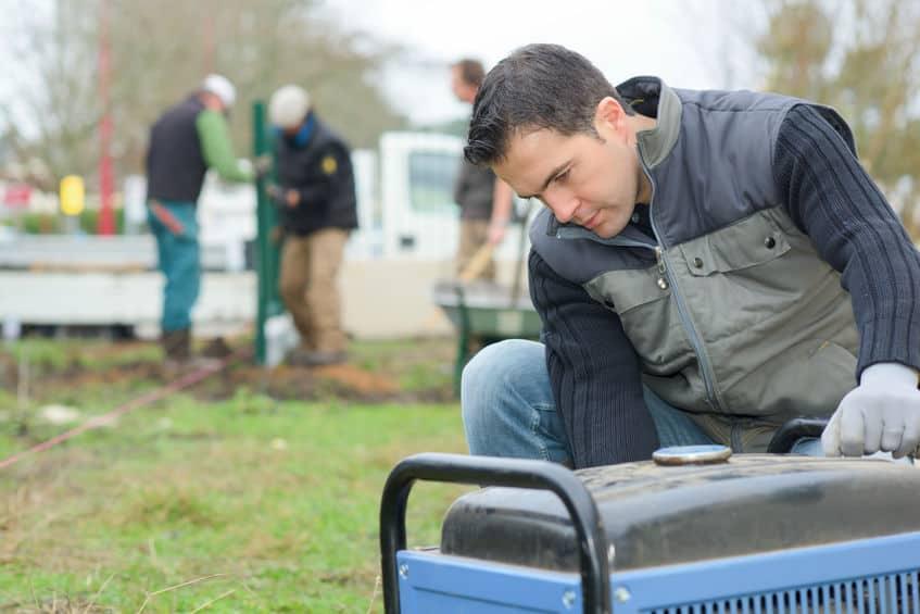 Homem mexendo em compressor de ar em obra ao ar livre.