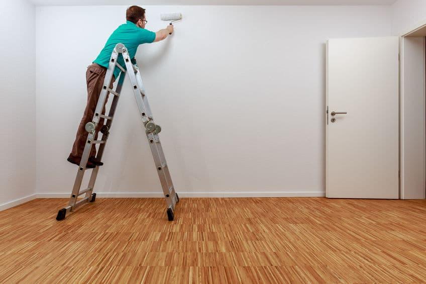 Um homem pintando a parede de uma casa.