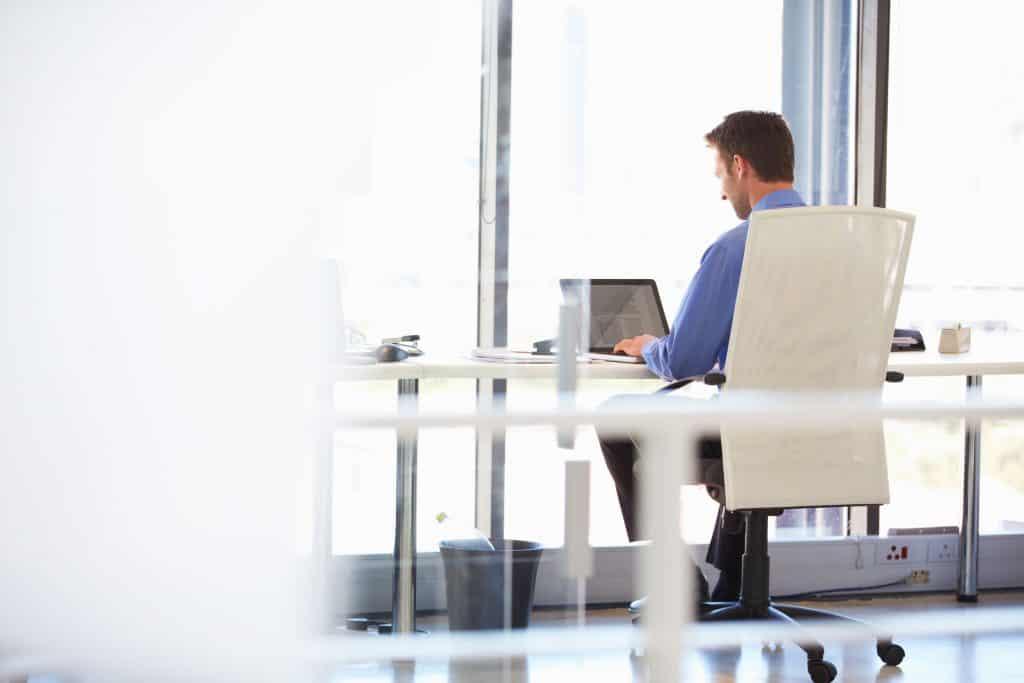 Imagem de uma homem de costas sentado em sua cadeira em seu escritório