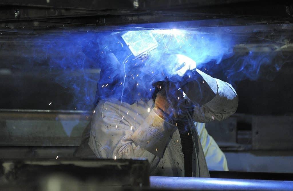 Uma pessoa soldando um material e fazendo fumaça por causa da soldagem.