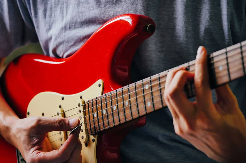 A man using plectrum to play guitar.