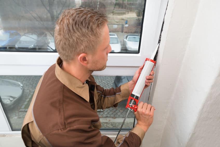 Imagem de uma homem utilizando uma pistola de silicone para aplicar o produto em uma parede.
