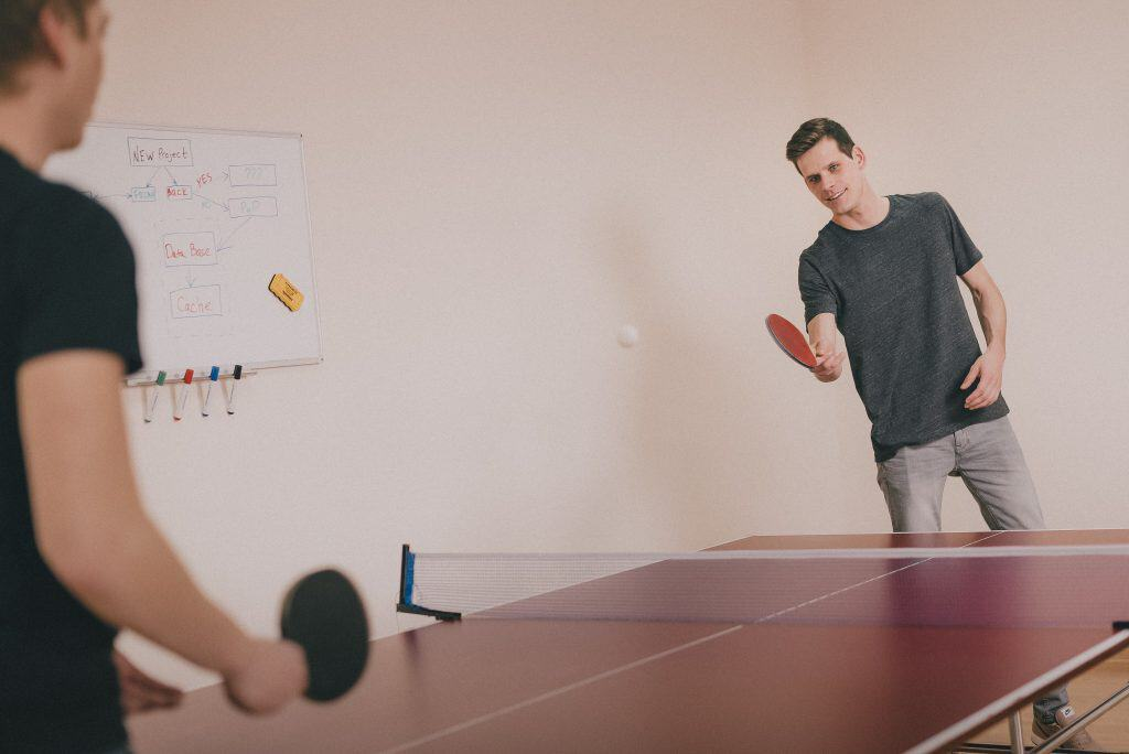 Na foto dois homens jogando tênis de mesa.