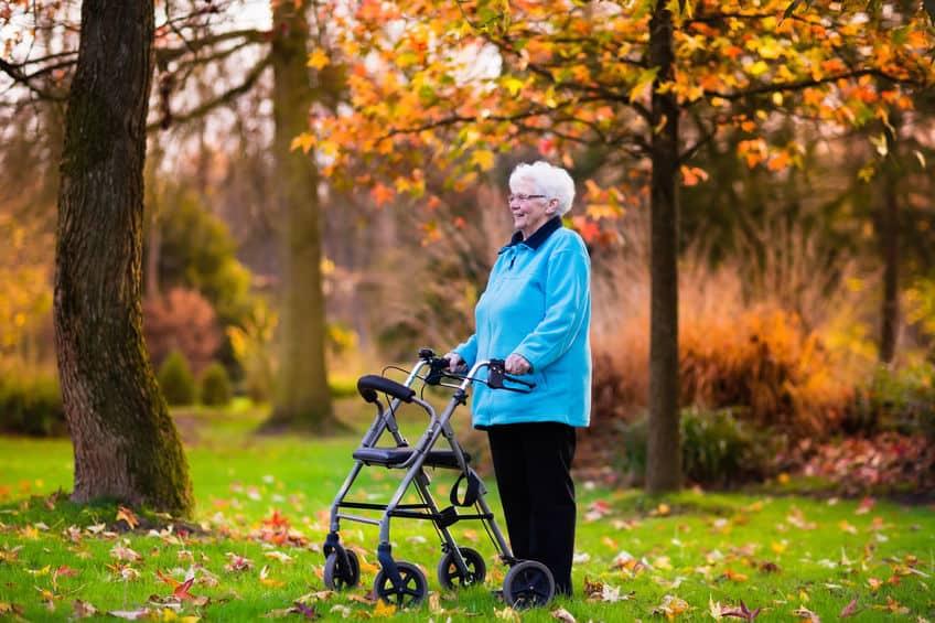 Imagem de idosa em parque com andador de rodinhas.