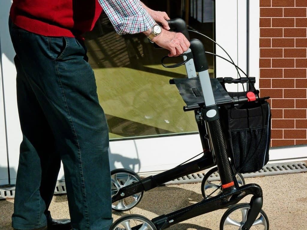 Imagem de um idoso andando com andador.