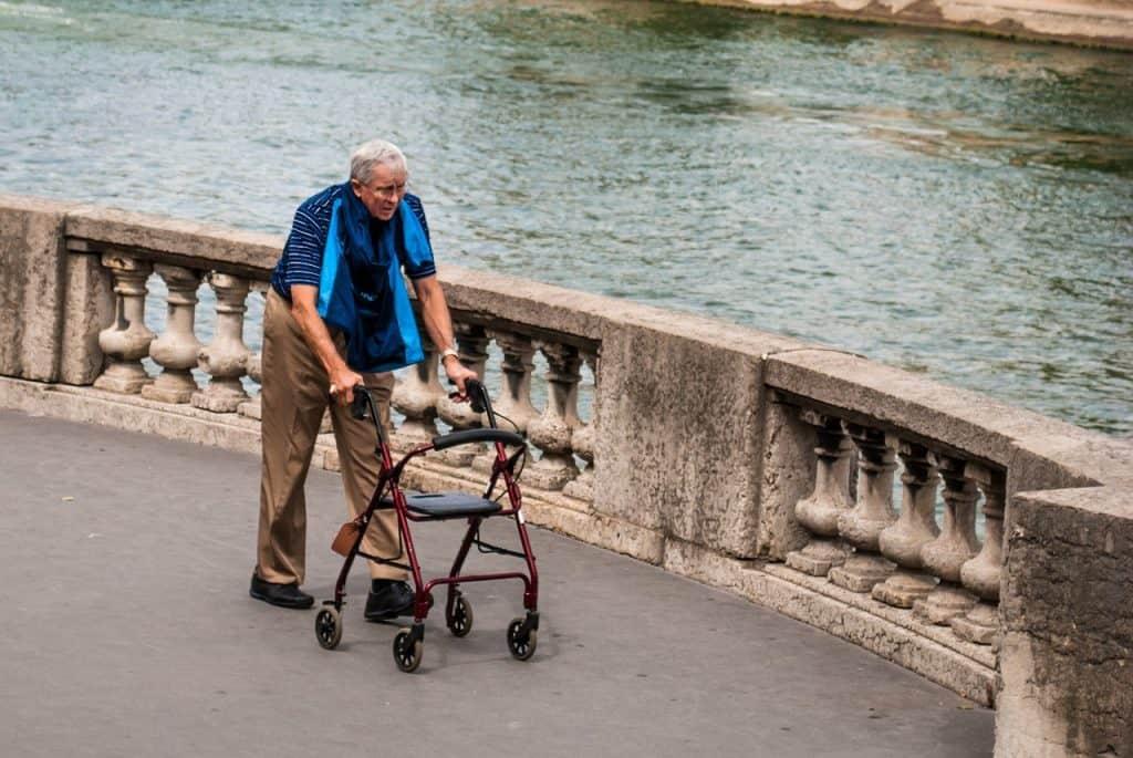 Imagem de um idoso caminhando com um andador.