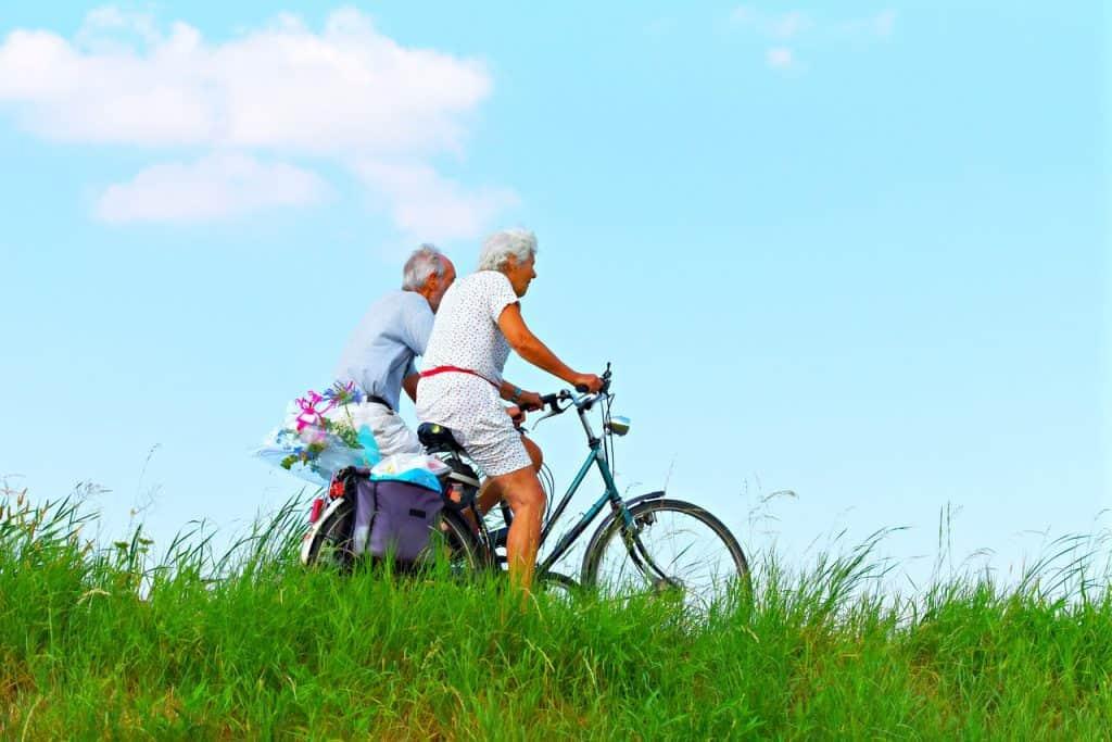 A imagem mostra um casal idoso andando de bicicleta em um campo.