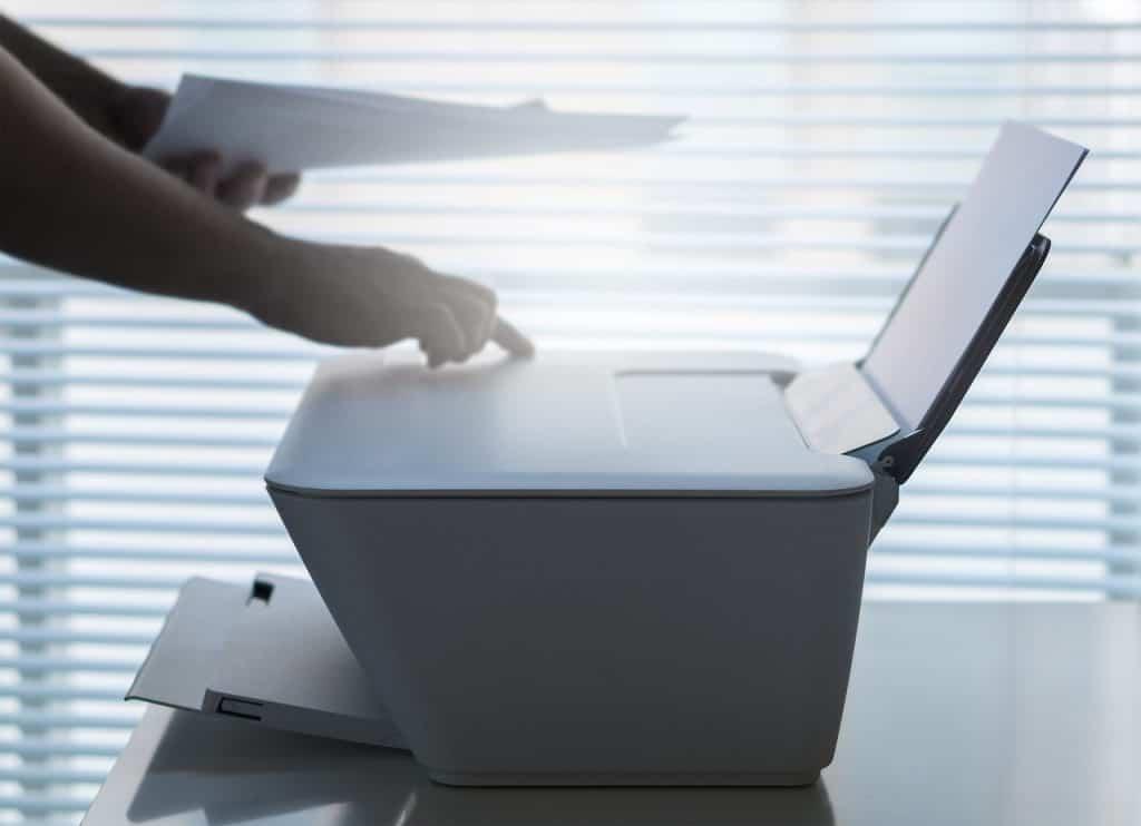 Imagem de pessoa segurando folha em frente a impressora.