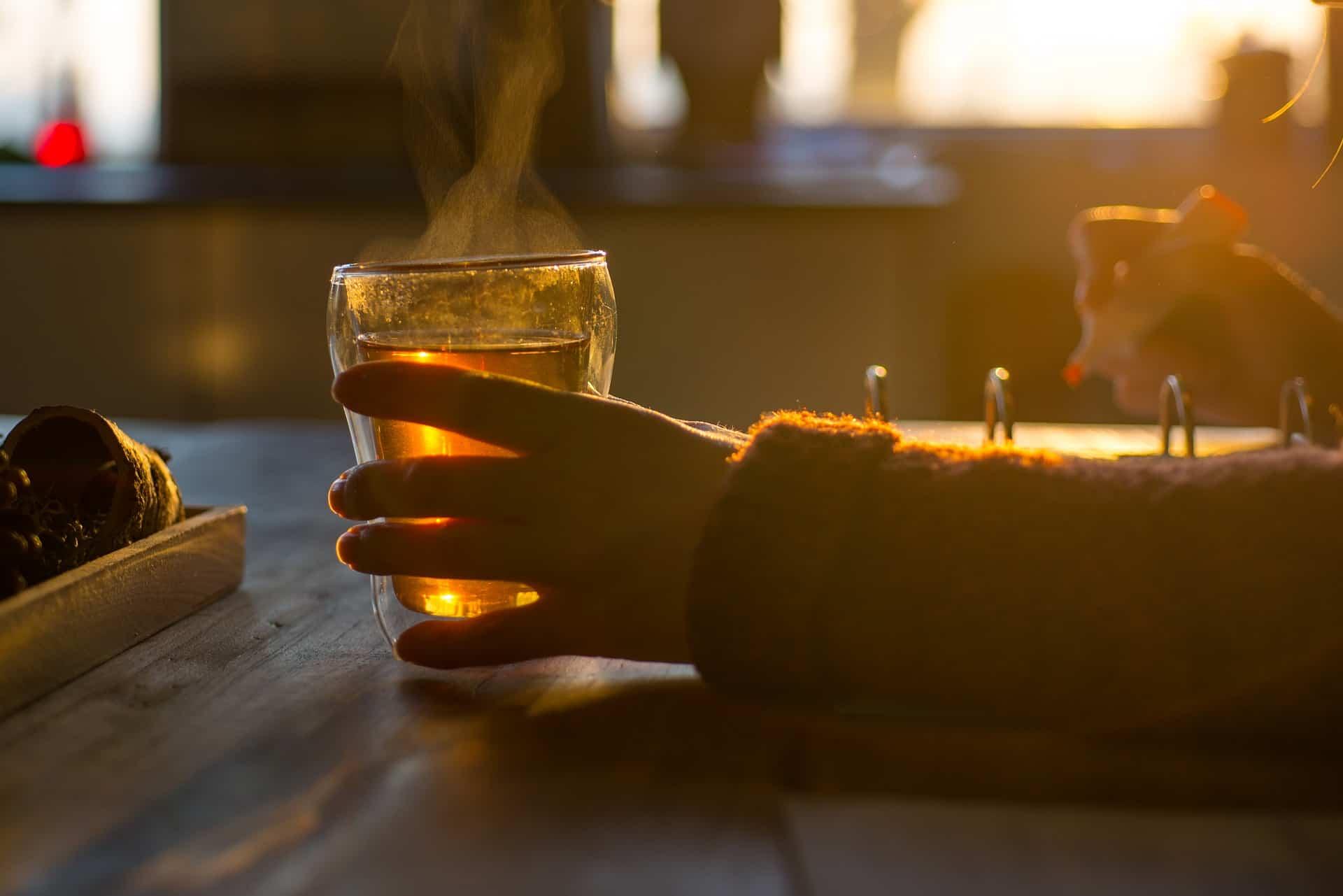 Imagem de mulher tomando chá quente preparado com infusor em copo de vidro enquanto estuda.