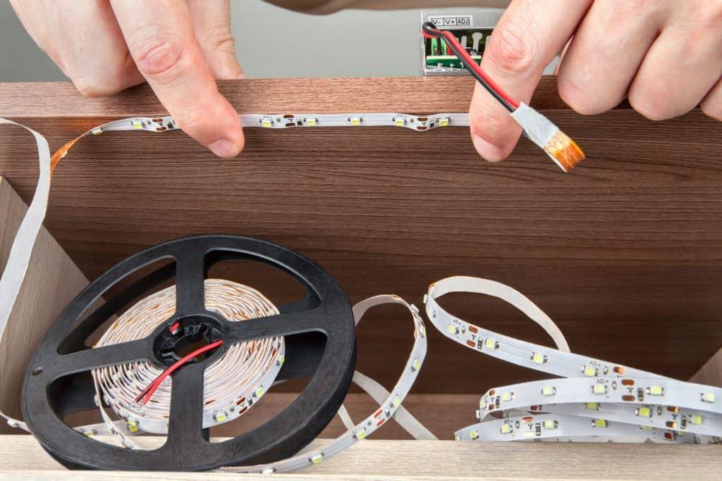 Mão de homem instalando fita de LED.
