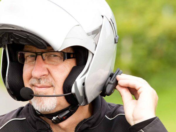 Imagem mostra um homem usando um intercomunicador para moto acoplado a seu capacete.