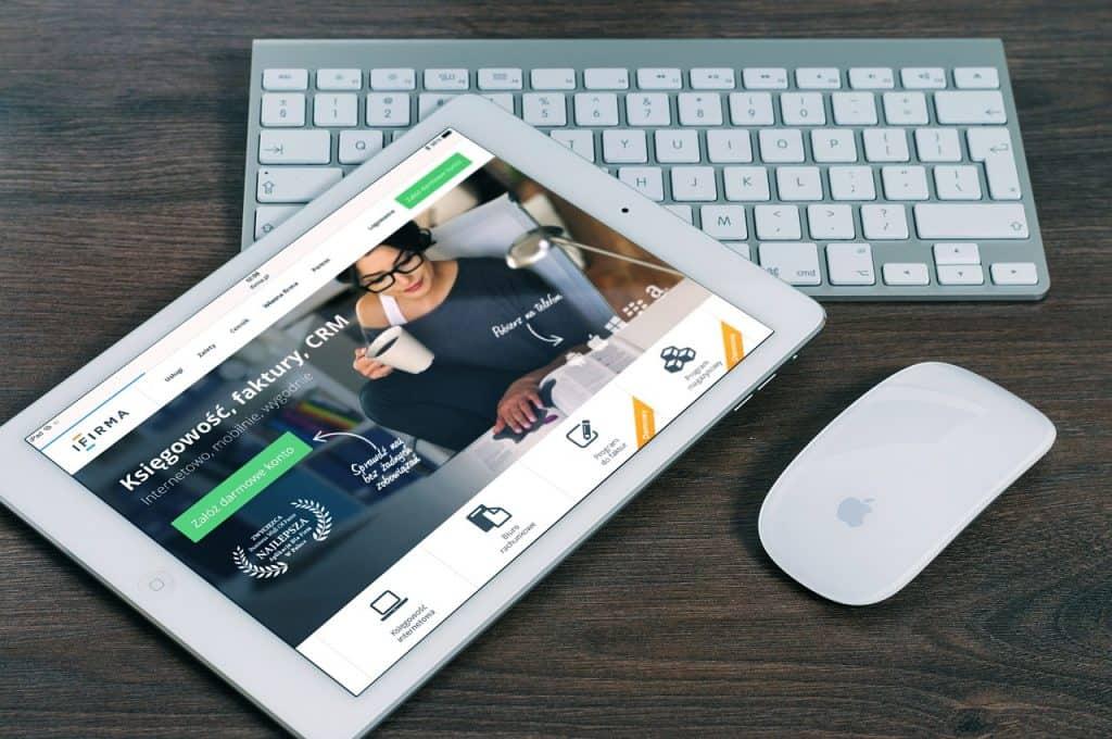 Imagem um iPad sobre meso ao lado de mouse e teclado da Apple.