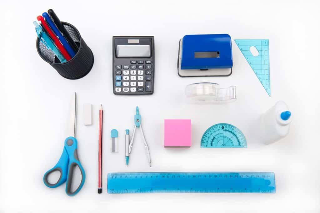Na foto uma mesa com régua, lápis, canetas, calculadora, cola, tesoura e outros materiais escolares.
