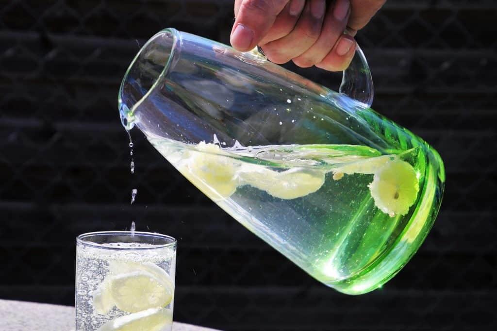 Imagem de uma pessoa despejando a água de uma jarra em um copo.