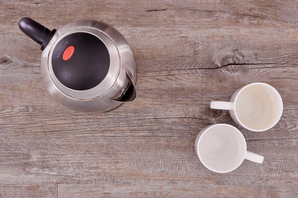 Imagem de jarra elétrica e xícaras sobre mesa.