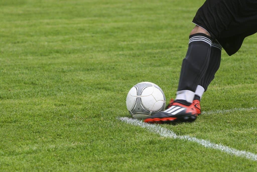Imagem mostra em close o chute do goleiro para a reposição de um tiro de meta. Ele ataca a bola com o pé esquerdo, deixando em evidência o volume protuberante de sua caneleira.