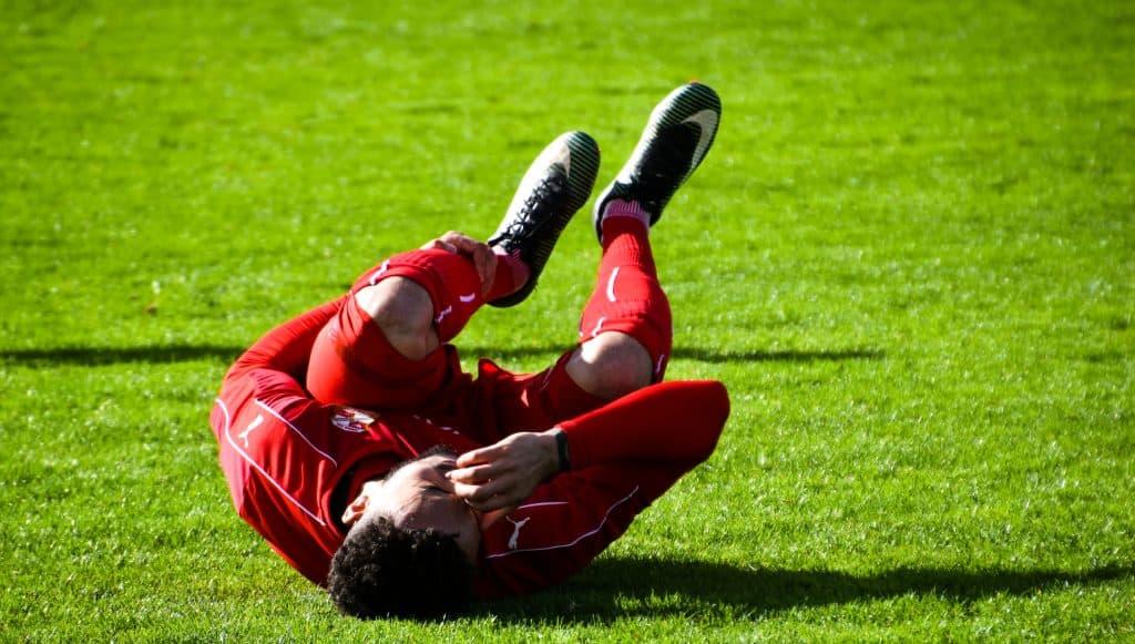 Imagem mostra um jogador caído no gramado, de barriga para cima e pernas recolhidas. Uma de suas mãos está sobre o seu rosto, enquanto a outra segura a canela de sua perna direita.