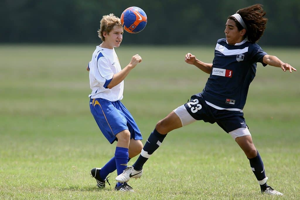 Imagem mostra dois rapazes jogando bola, adversários, lado a lado. A bola está no alto, enquanto há um contato do pé do jogador da direita na canela do jogador da esquerda.