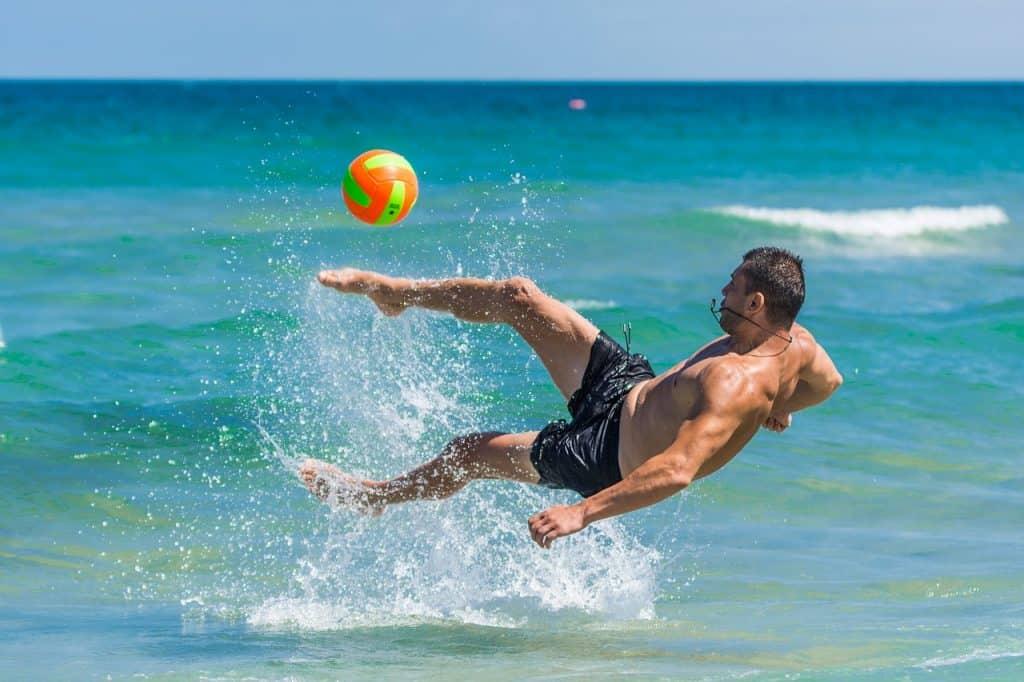 Imagem destaca homem dentro do mar chutando uma bola colorida.