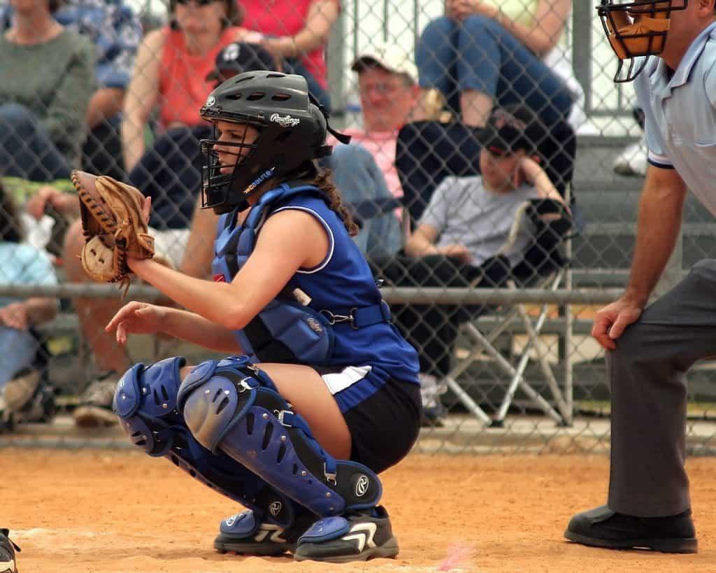 Imagem de mulher agachada jogando softbol.