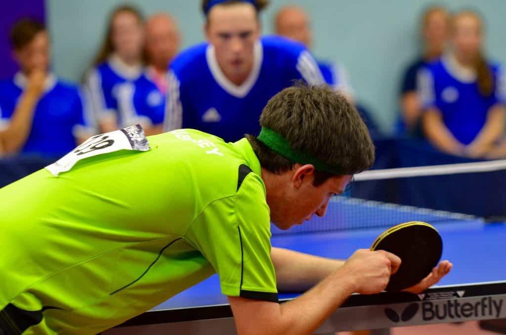 Na foto duas pessoas jogando tênis de mesa.