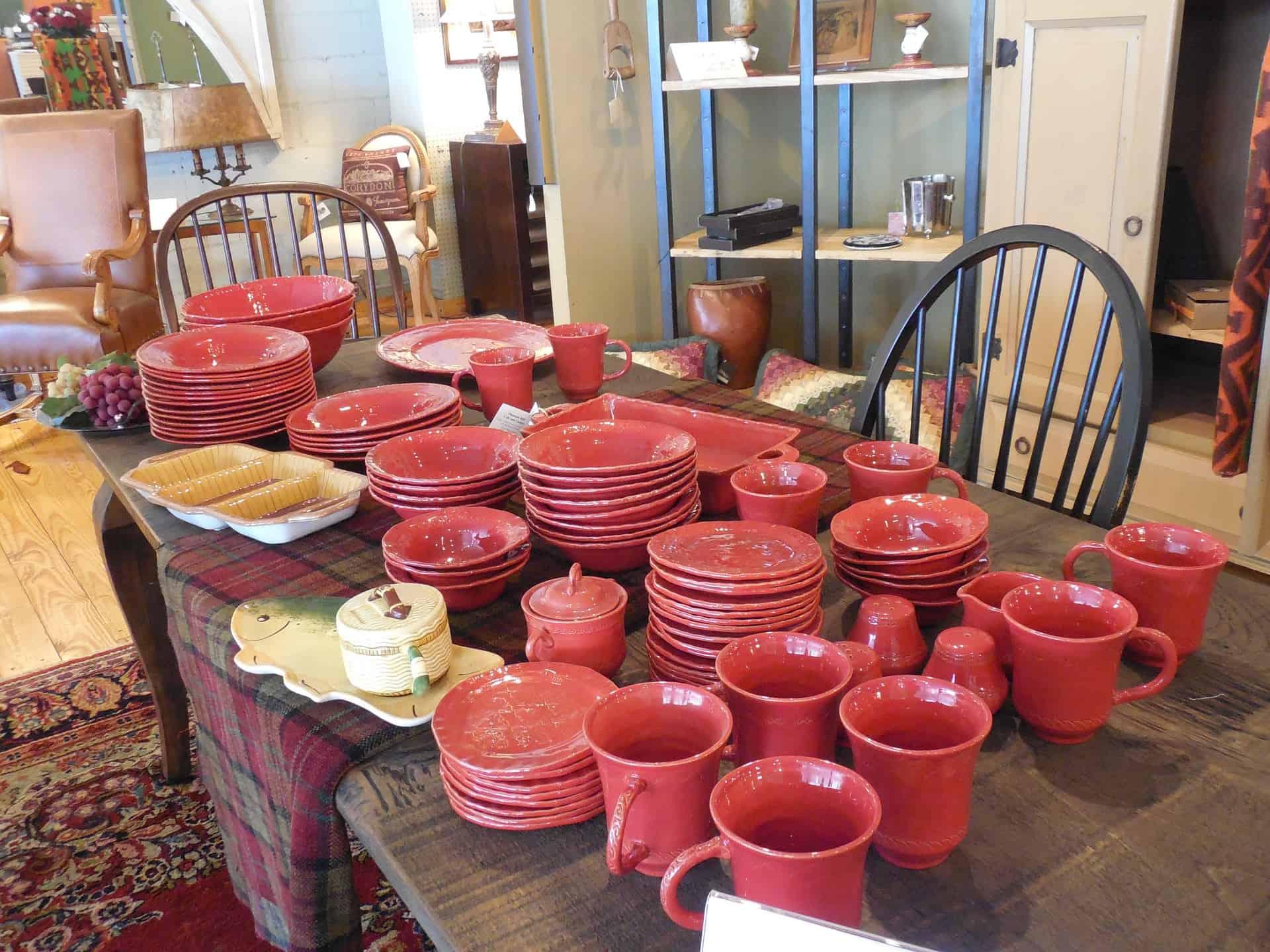 Foto de diversos jogos de pratos e xícaras vermelhos sobre mesa de madeira.