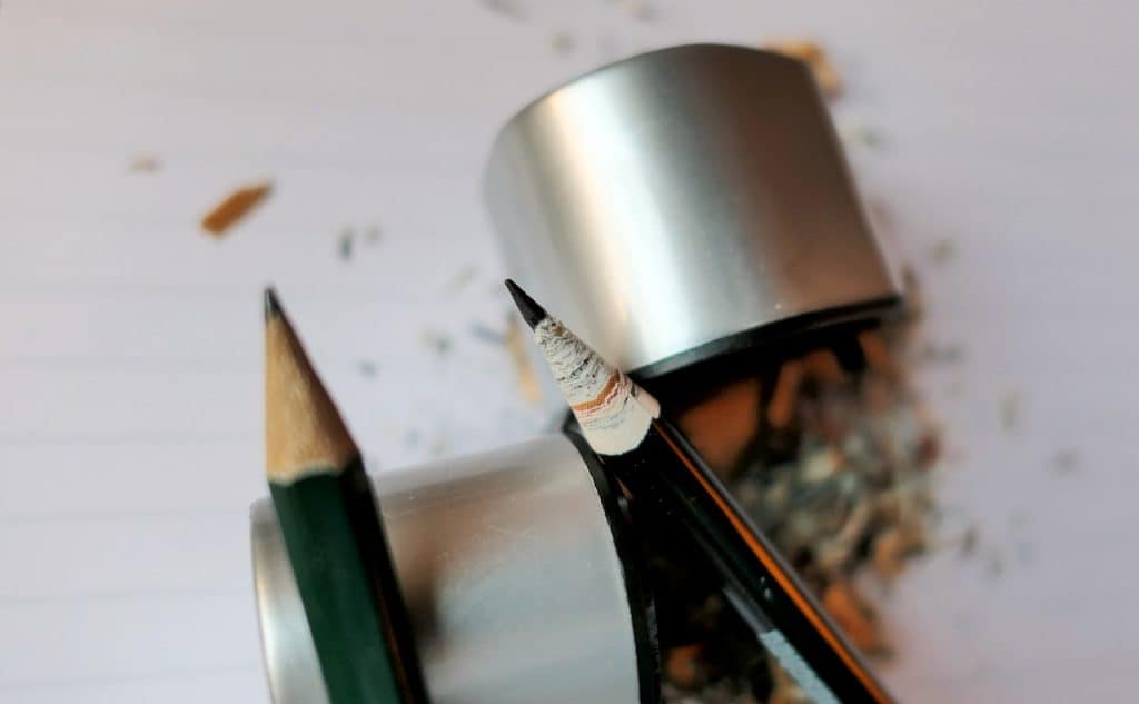 Lápis e apontador com depósito em meio às lascas.