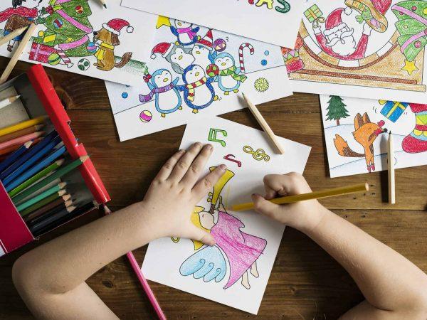 Imagem de criança utilizando lápis de cor para colorir desenhos com temática de natal sobre mesa de madeira.