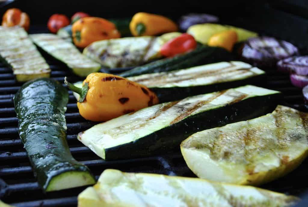 Na foto é possível ver alguns legumes assando em uma churrasqueira.