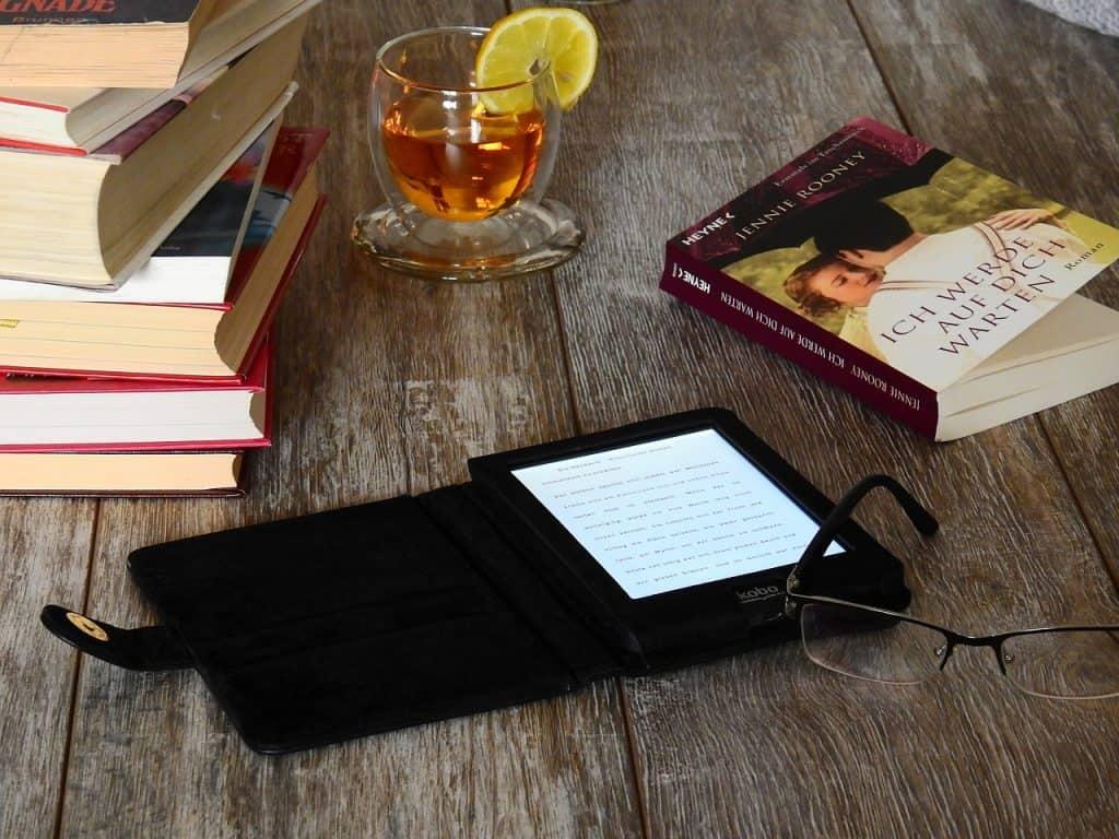 Foto de um kindle ligado com capa aberta, ao lado de vários livros, uma xícara de chá, e um óculos de grau.
