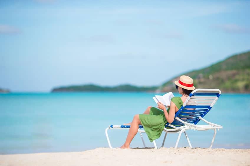 Imagem de mulher lendo em espreguiçadeira na frente do mar.