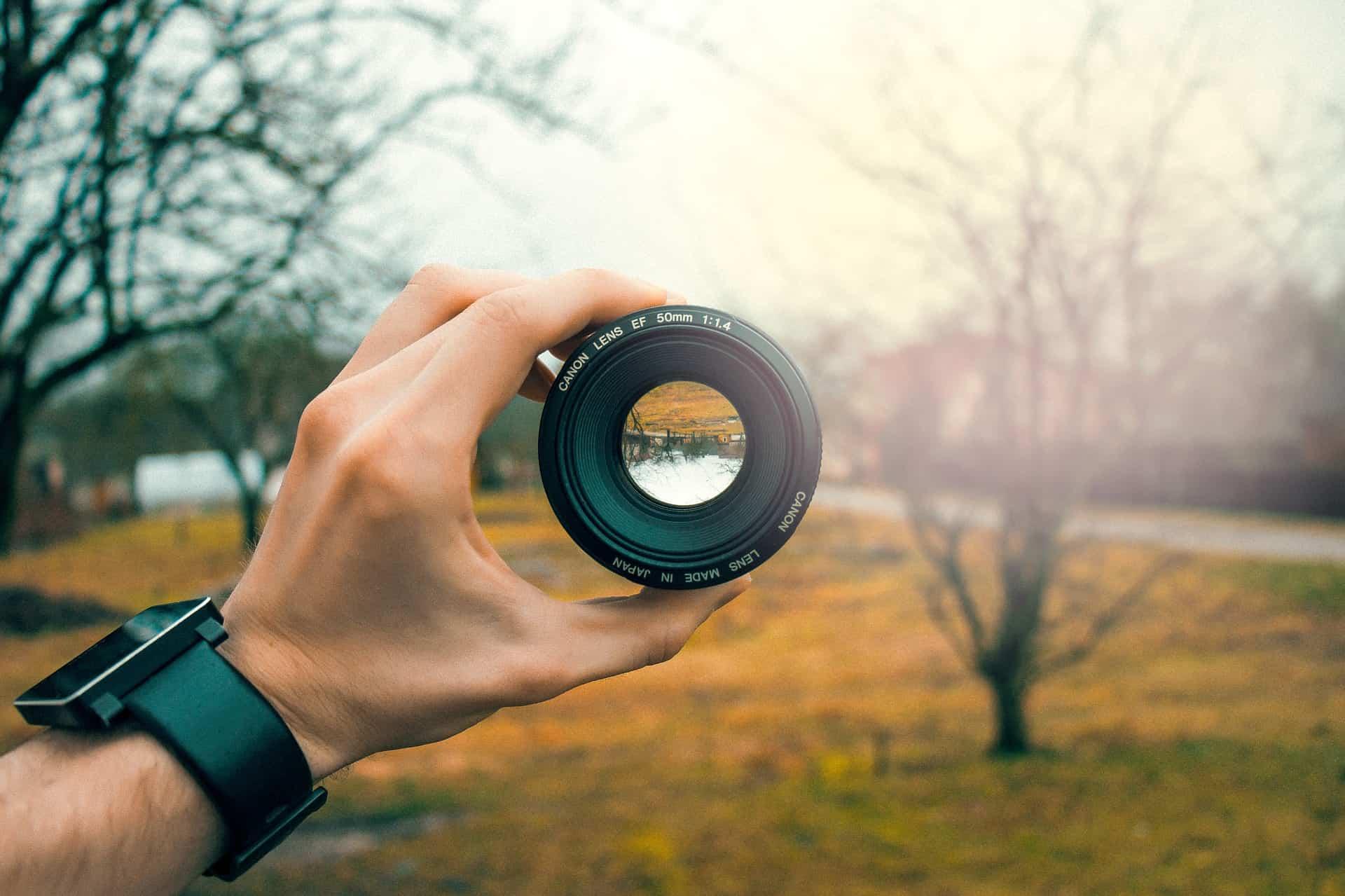 Imagem mostra a mão de uma pessoa segurando uma lente Canon em frente a um campo com árvores.