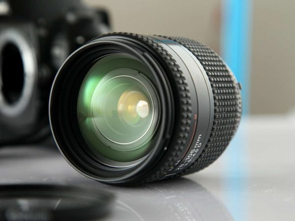 Na foto está uma lente de câmera fotográfica em cima de uma mesa.