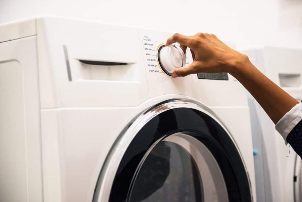 Imagem de uma mulher programando uma lavadora.