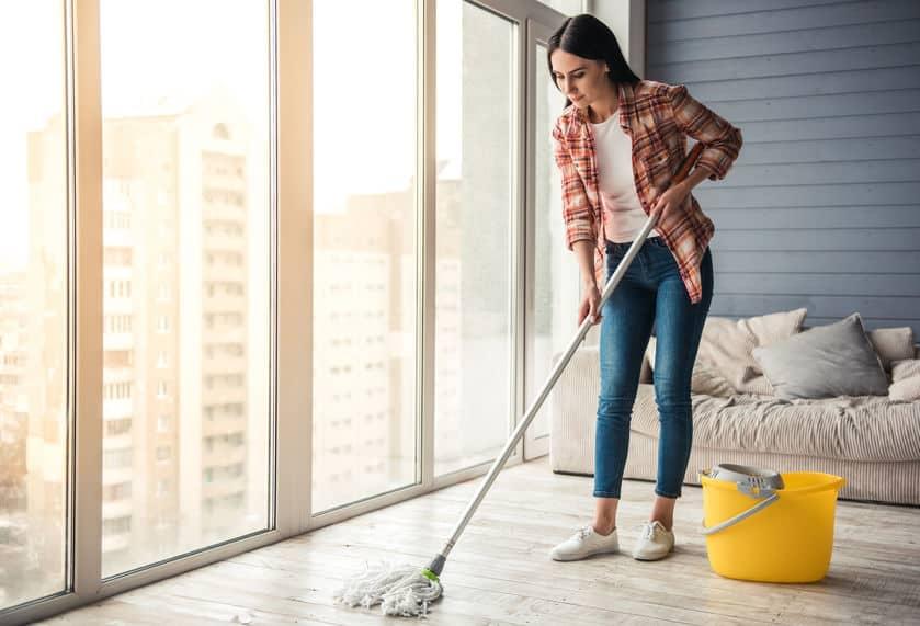 Imagem de uma mulher limpando o chão da sala com um mop e balde amarelo.