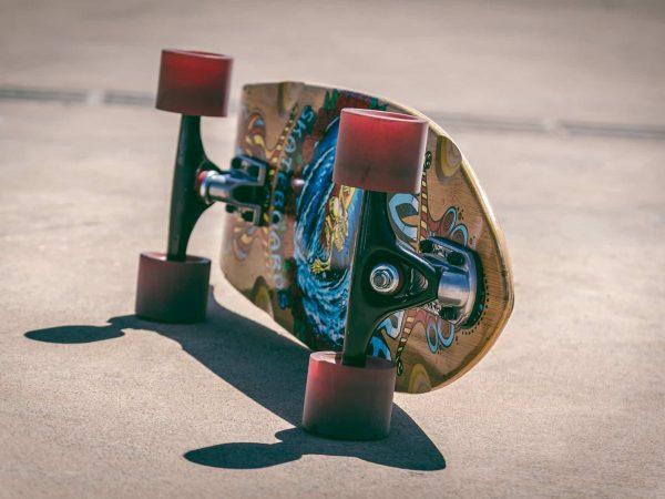 Imagem mostra um longboard com duas rodas apoiadas lateralmente no chão, deixando a pintura do shape à mostra.