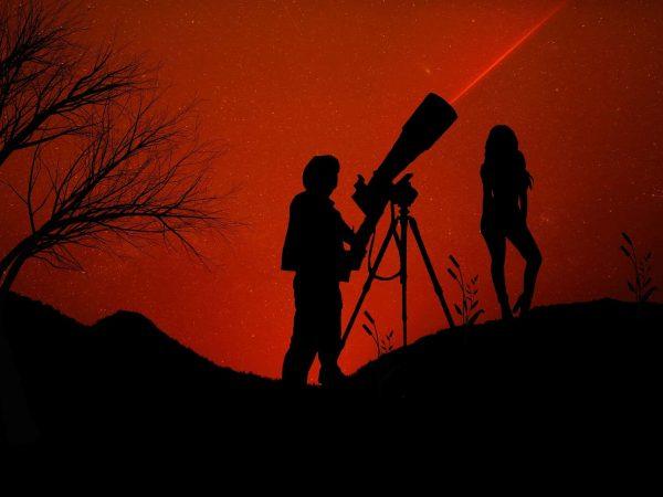 Pessoas usando luneta para ver estrelas.