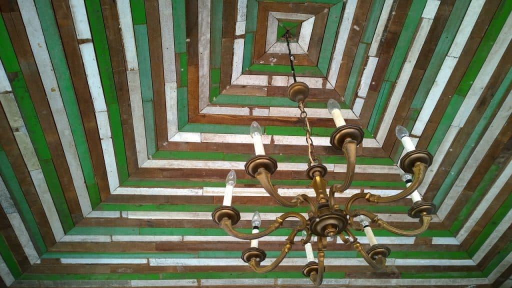 Imagem de lustre rústico no estilo candelabro com armação em metal pendurado em telhado de madeira verde, branca e marrom.