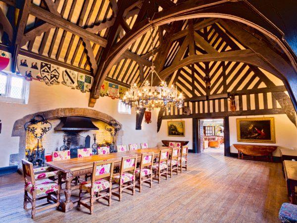 Imagem de salão medieval com decoração em madeira com lustre rústico de madeira e metal.