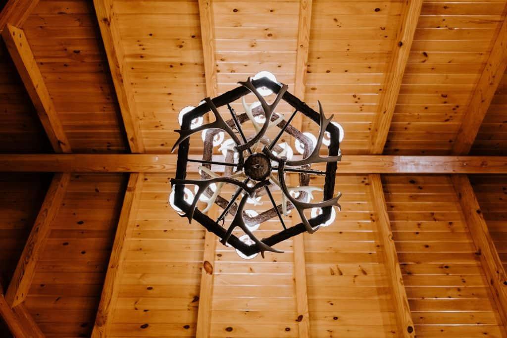 Imagem de lustre rústico de madeira com ornamento de chifres pendurado a teto de madeira.