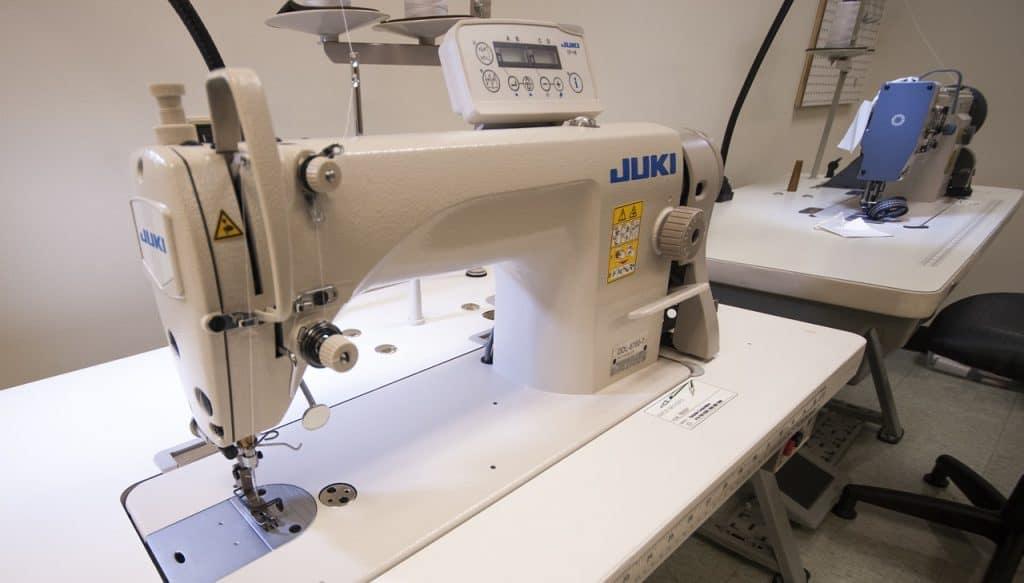 Na foto estão duas máquinas de costura profissionais brancas dentro de uma sala.