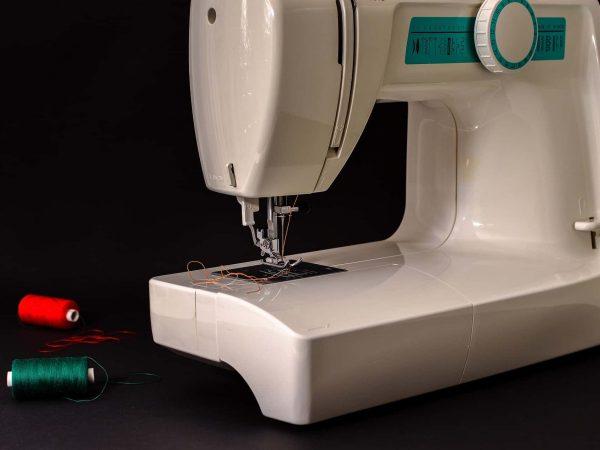 Na foto está uma máquina de costura branca com detalhes azuis, com dois retrós de linha, um verde e um vermelho ao lado. O fundo da imagem é preto.