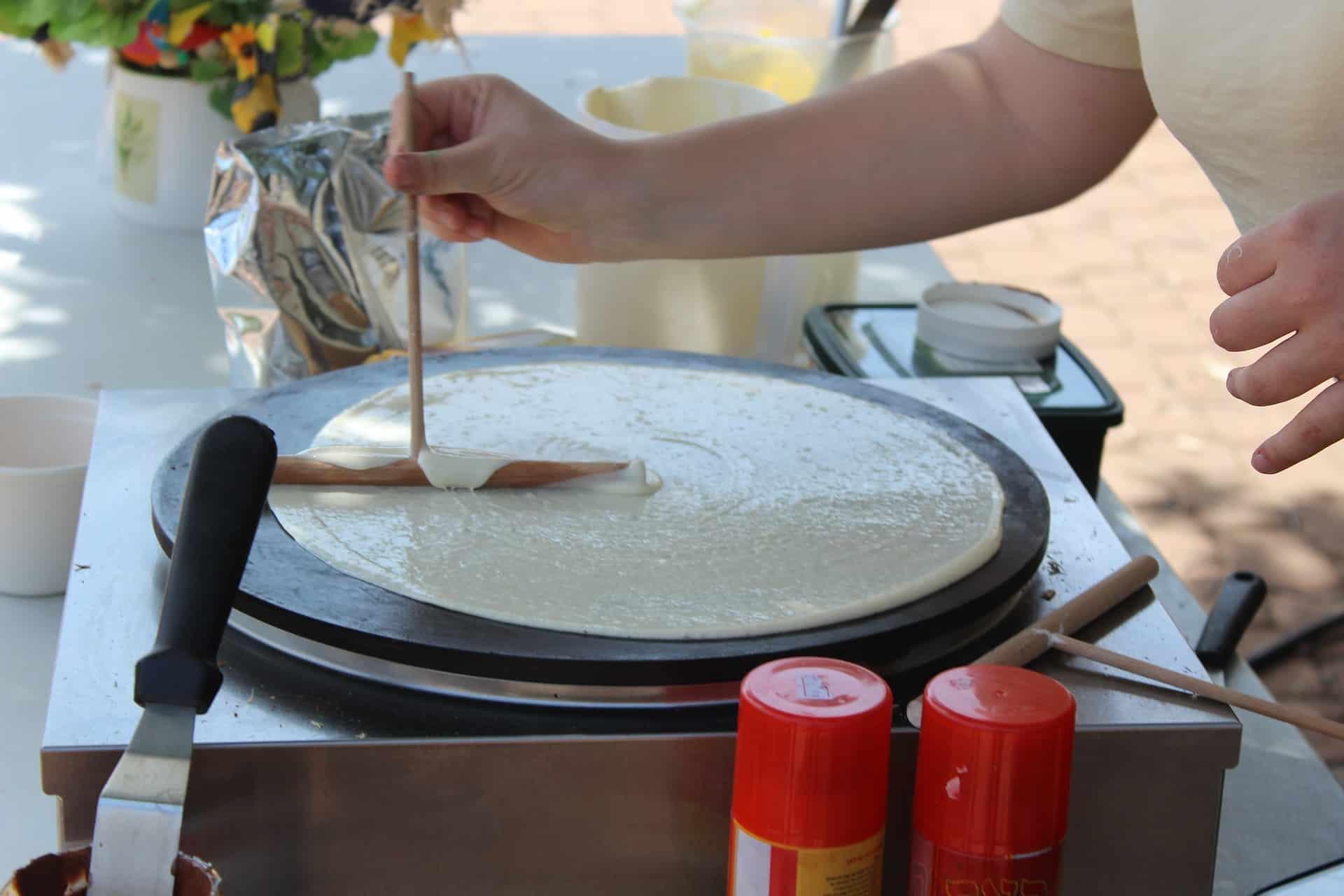 Imagem de uma pessoa preparando um crepe em estilo francês.