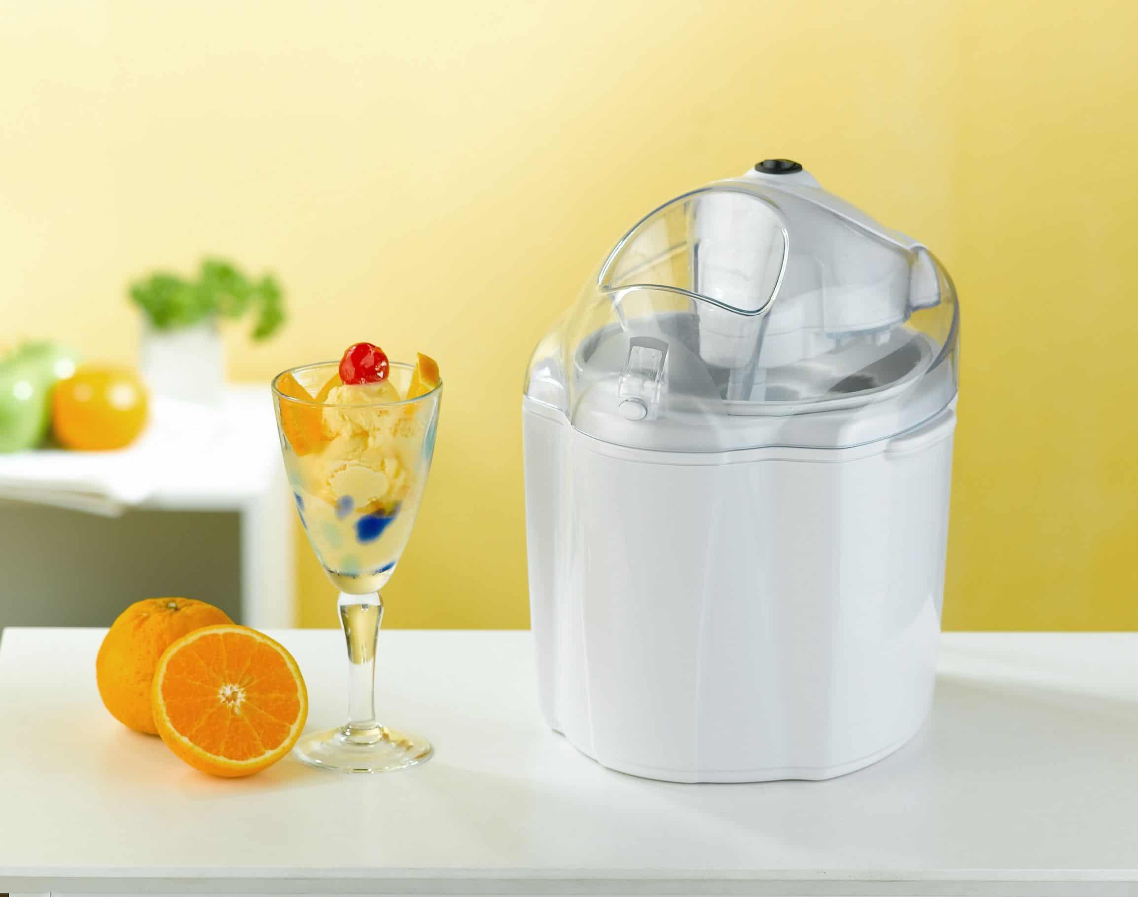 Imagem mostra taça de sorvete de frutas ao lado de máquina de sorvete doméstica com laranjas ao lado e outros ingredientes desfocados ao fundo.