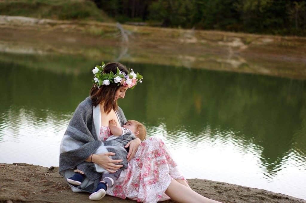 Foto de uma mulher sentada próximo a um rio, amamentando um bebê. Ela veste uma coroa de flores na cabeça, um vestido floral e um casaco cinza.