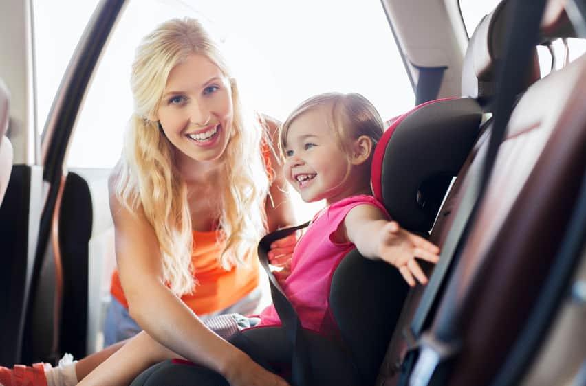 Mãe colocando menina em cadeirinha de bebê para carro.