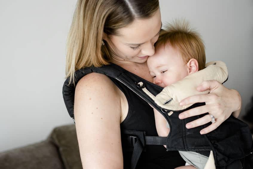 Imagem de mãe segurando filho que está em um canguru.